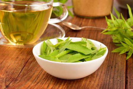 レモンバーベナは、木製のテーブルの上の白いボウルとバーベナ茶葉します。レモンバーベナ。