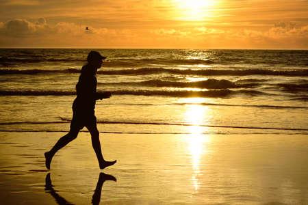 barefoot man: Barefoot man running at ocean beach at sunset gold in early autumn. Runner workout evening. Outdoor activity.