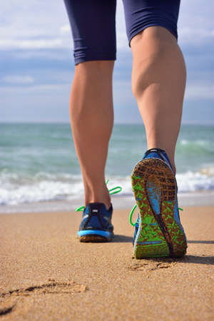 woman foot: Womans legs, a runners legs against ocean beach. Female running shoes of a jogger walking outdoors. Shallow depth of field, focus on right foot.