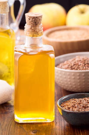 linum usitatissimum: Nonrefined flaxseed oil in a bottle and brown flax seeds in bowl on wooden table. Vertical shot Stock Photo