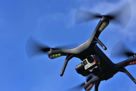 Black drone with camera flying over blue sky. Angle view, copy space. Stock Photo