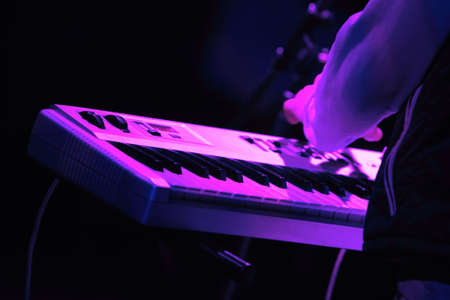 Rock concert series: synthesizer keyboard and musician's arm, lit by purple and blue Stock Photo