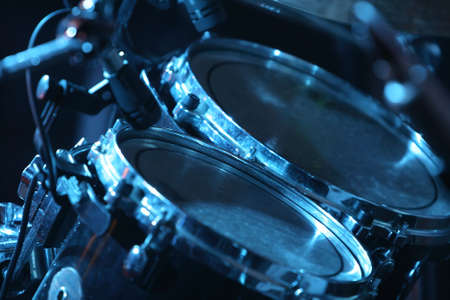 Rock concert series: drum set with microphones, lit by blue Stock Photo