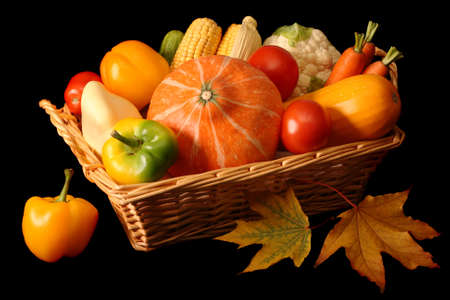 Basketful of autumnal vegetables, isolated on black background Stock Photo