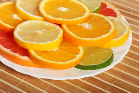 Plateful of citrus slices, on bamboo mat Stock Photo - 3502606