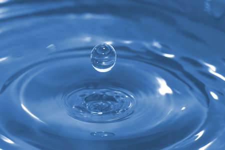High-speed photo of a water drop frozen in time after it has impacted and rebounded a body of water.  Narrow DOF.