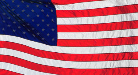 American or United States Flag blowing in the wind with backlighting Stock Photo