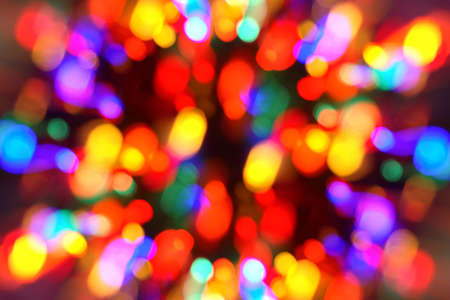 A time-lapse photo of defocused Christmas tree lights while zooming out to give it a feeling of movement and motion. Stock Photo