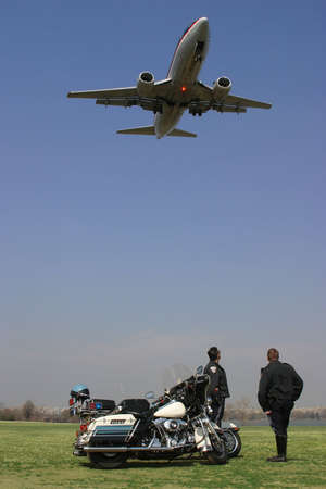 Photo of two motorcycle police watching a jet aircraft fly overhead as it is about to land.  Taken on location at Gravely Point Park near Ronald Reagan National Airport just outside of Washington, DC, USA.