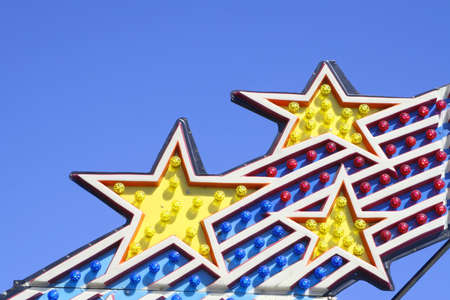 Closeup of Amusement Park Ride Lights Against Clear Blue Sky