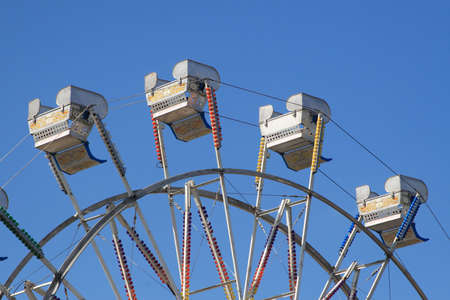 Empty ferris wheel chairs at the North Carolina State Fair set against clear blue sky Stock Photo