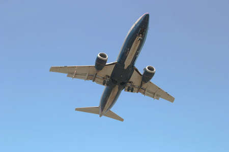 Photo of a jet airliner as it is passing overhead and about to land.