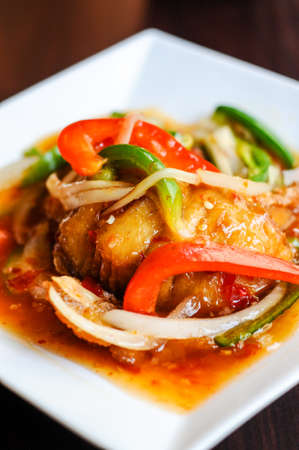 Red Hot Snapper, Fried red snapper fillet topped with hot peppers, onions, fresh garlic & bell peppers mixed in sweet & sour sauce. Stock Photo