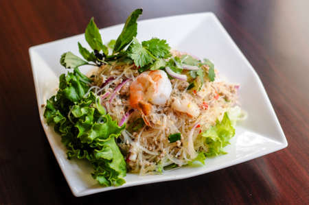 Yum Woonsen Glass Noodle Salad, Glass noodles salad served on a bed of lettuce with chicken and shrimp. Stock Photo