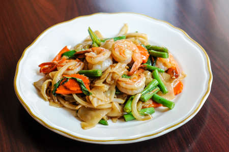 Pad Khee Mao, Stir-fried with wide rice noodles, hot peppers, carrots, green beans, onions, tomato and sweet basil leaves.