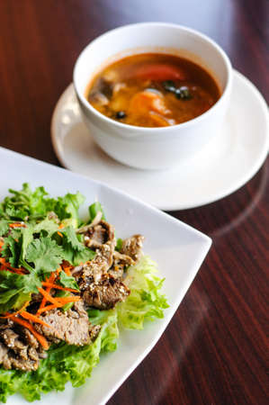 Nam Tok Spicy Beef Salad, Char-broiled tender slices of beef mixed with red onion, green onions, roasted rice, cilantro, chili powder & citrus leaves Stock Photo