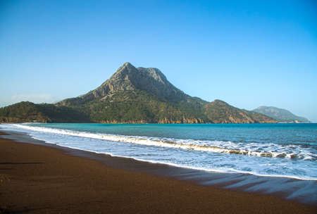 Mediterranean beach with a mountain in the background Stock Photo