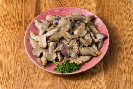 Fried mushrooms on a lilac plate stands on a beautiful wooden background