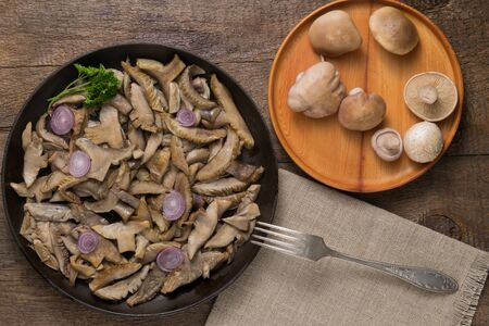 Delicious fried mushrooms in pan on table