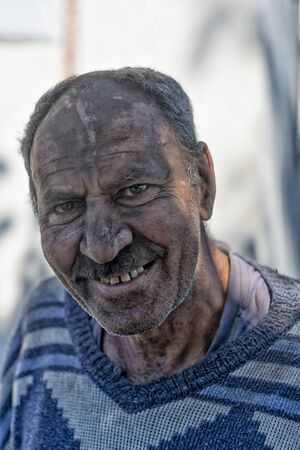 Portrait of an elderly smiling man with a face in black dust