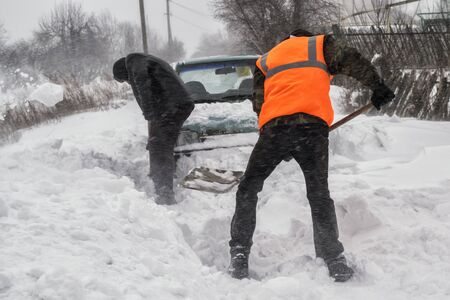 transportation, winter, people and vehicle concept - closeup of man digging snow with shovel near car landscape