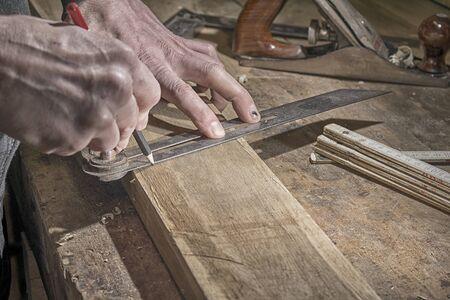 Carpenter marking measurements on piece of wooden board Banco de Imagens