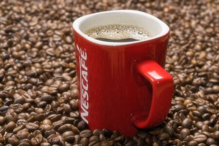 red mug of Nescafe on the background of scattered coffee beans