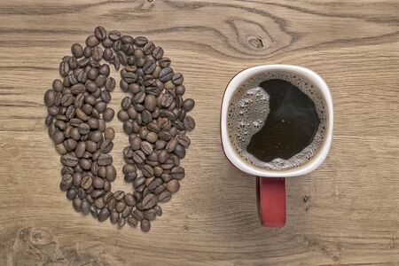 red mug on the background of scattered coffee beans 写真素材