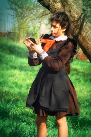 Girl in a school uniform and tie with a smartphone in her hand on the background of a tree... Portrait