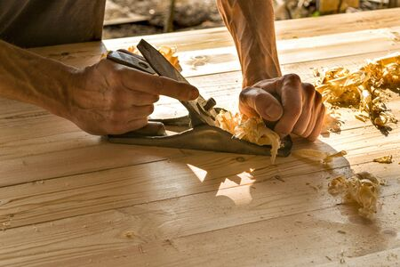 Joinery. Planing a natural wood furniture panel with a manual planer. Hands with a planer. 写真素材