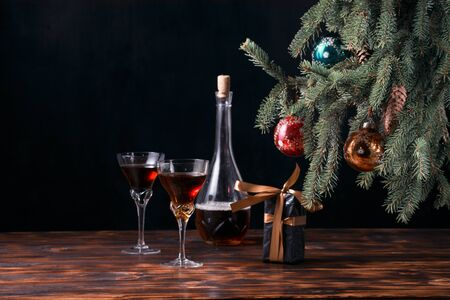 The Christmas tree with cones is decorated with multi-colored glass balls on a black background, under it on the table are out of focus two glasses of a bottle and a gift with a ribbon. For the holiday of Christmas and New Year.