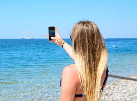 mujer mirando el horizonte: Beautiful girl with a mobile phone on the beach Foto de archivo