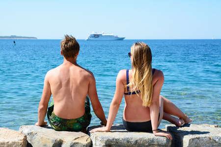 Boy and girl looking at the sea horizon