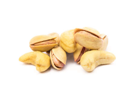 Pile of roasted pistachios and cashew isolated on white background