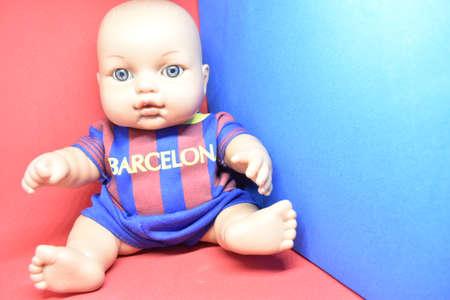 In red and blue fan doll in Barcelona jersey.