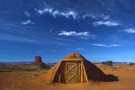 Hogan, the traditional Navajo red clay earth house, with backdrop of famous table mountains of the Navajo National monument on the background