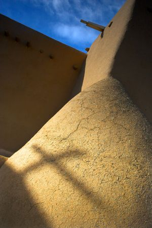 Shadow of the cross on the orange clay wall of the famous landmark of the adobe church in Taos with the background of blue sky photo