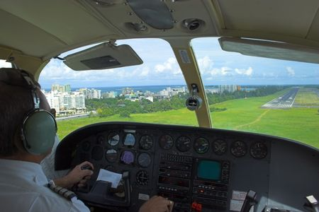 Pilot is getting ready for landing overlooking the city, ocean, beach and landing strip on the background.   photo