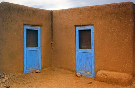 adobe pueblo: Two nearly identical blue doors leading to the ancient adobe dwellings made or orange stone and clay. Stock Photo