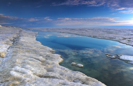 Shore of the Arctic Ocean covered with snow and ice, Blu sky with clouds is reflected in the water strip located in the crack of the ice shield.