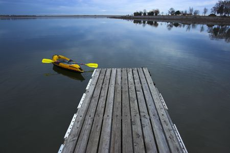 Kayak on the lake attached to a wooden pier on the background of evening sky and forest reflection photo