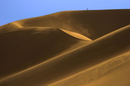 Tiny backpacker tourist hiking against blue sky at the top of the giant sand dune wet after the rain during low sun.