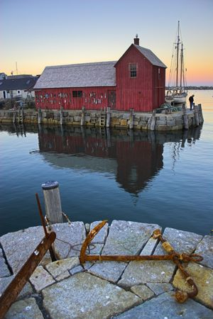 Most photographed famous fishing shack in New England on the background with antique anchors on the foreground.