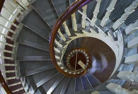 Famous landmark of Old State House in Boston. Photo of the spiral stairs of the person intentionally blurred holding the rail and moving down.  photo