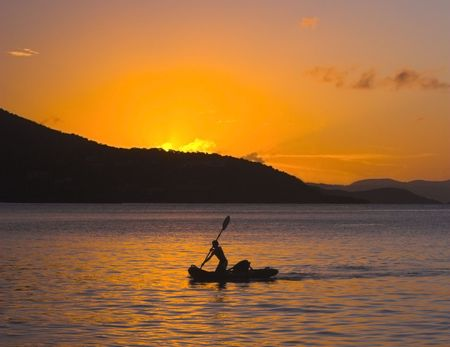 Native boy paddling down to the shore during the sunset after a day of fishing.