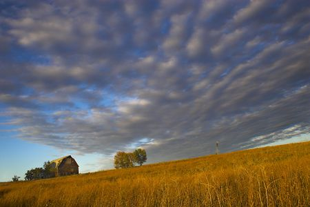 "Farm building with spectacular sky during last moments of the sunset with sign saying ""Little Hill Side Farm""on the background and prairie in the foreground photo"