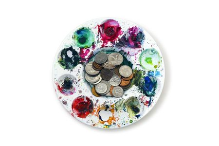 Change coins positioned in the middle of the artists palette with multiple paint colors photo