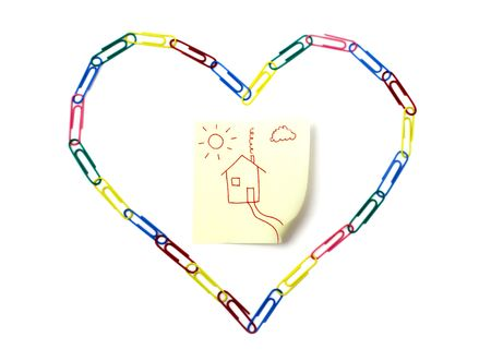Paper clips arranged in the shape of heart around post-it note on the white background to symbolize love for home, home loan, home improvement ect. photo