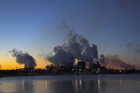 Factory over the river with smoke coming out of the chimneys Stock Photo