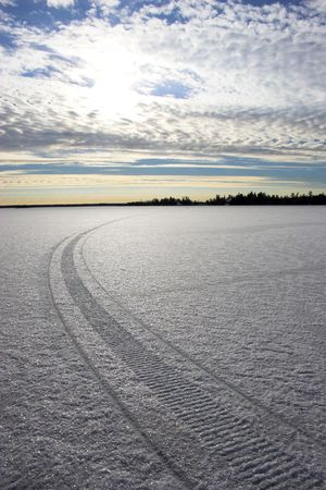 Snowmobile route over frozen lake with colorful reflections of the sun in snow crystals